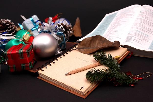 Decorazione natalizia e bibbia con sfondo nero.