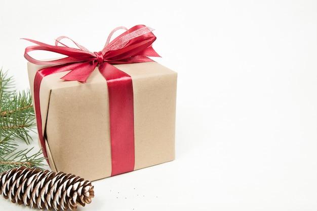 Decorazione natalizia, grande confezione regalo con fiocco rosso, ramo di un albero di natale e grande cono di natale isolato su sfondo bianco