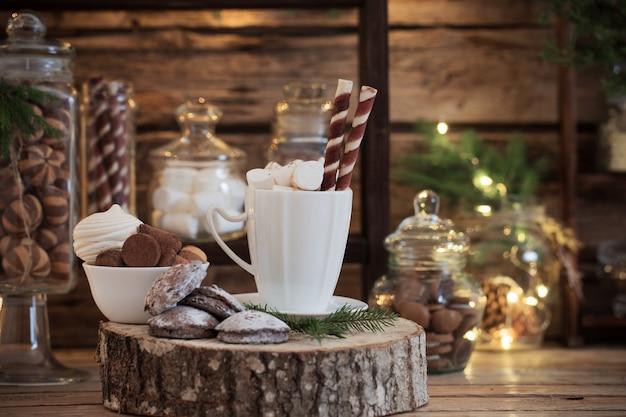 Barra di cacao della decorazione di natale con biscotti e dolci su fondo di legno vecchio