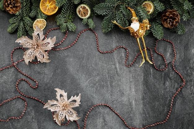 Decorazioni natalizie su un cemento scuro con rami di un albero di natale perline coni di frutta secca e giocattoli