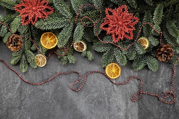 Decorazioni natalizie su un cemento scuro con rami di albero di natale perline frutta secca e coni