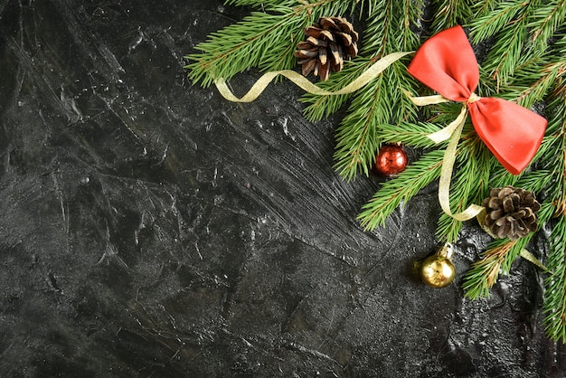 Decorazione natalizia. ramo di abete con palline, regali, pigna e fiocchi su una superficie di legno nera