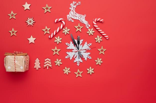 Decorazioni natalizie a forma di orologio su sfondo rosso e spazio libero per il testo