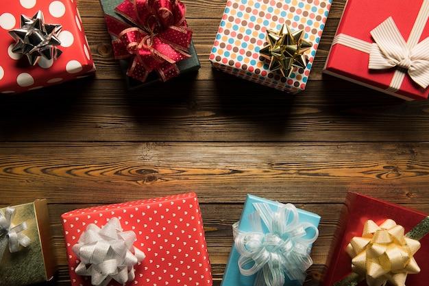 Contenitori di regalo della decorazione di natale sulla vista superiore del fondo di legno con copyspace per i telai, i regali e la decorazione festiva di natale
