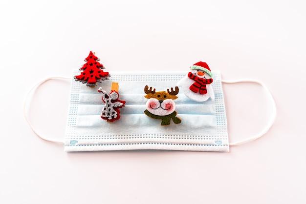 Decorazione natalizia isolata su sfondo bianco con maschere per evitare infezioni da virus