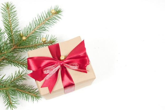 Decorazione natalizia, grande confezione regalo con fiocco rosso e ramo di un albero di natale con palline gialle isolato su sfondo bianco