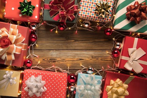 Luce di decorazione natalizia e scatole regalo su fondo in legno vista dall'alto con copyspace per cornici, regali e decorazioni festive di natale