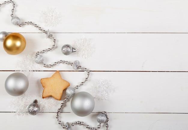 Decorazione natalizia fatta di palline d'argento, perline, coni e biscotti su legno bianco