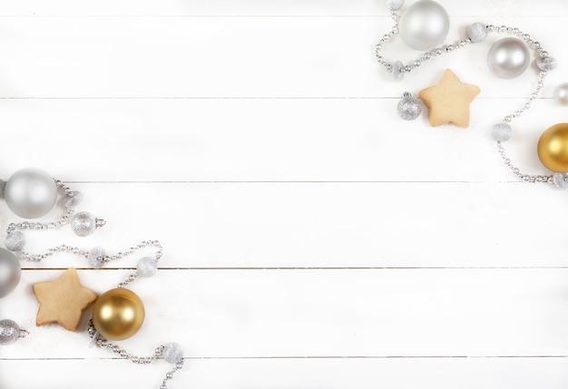 Decorazione natalizia fatta di palline d'argento, perline, coni e biscotti su una superficie di legno bianca