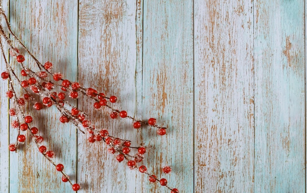 Bacche congelate rosse della decorazione di natale sulla superficie di legno rustica