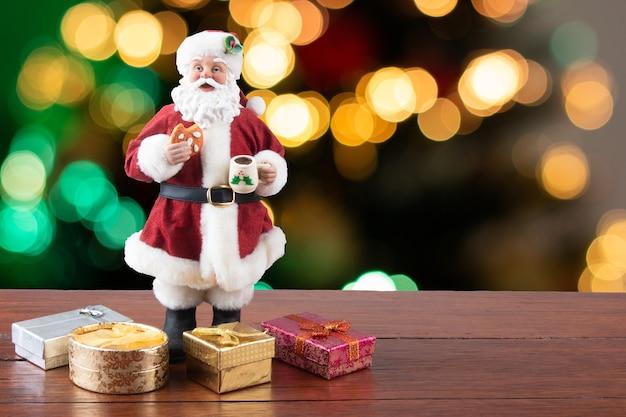 Decorazione natalizia babbo natale con doni su un natale sfocato.