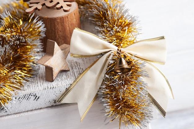 Decorazioni natalizie in interni scandinavi con fiocco dorato, campane e candela accesa. copia spazio per il saluto
