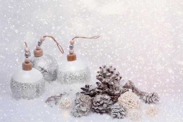 Decorazione natalizia in stile scandinavo. palline bianche con pigne e pezzi di corteccia di abete isolato su uno sfondo luminoso con fiocchi di neve e luci