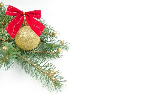 Decorazione natalizia, palla gialla lucida con un fiocco rosso su un ramo di un albero di natale isolato su uno sfondo bianco