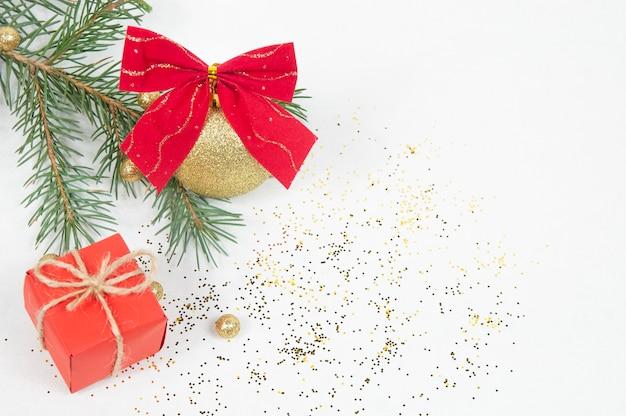 Decorazione natalizia, palla gialla lucida con fiocco rosso sul ramo di un albero di natale e confezione regalo rossa isolato su sfondo bianco