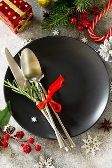 Tavola natalizia piatto nero festivo e posate con decorazioni natalizie