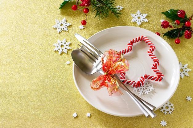 Tavola delle decorazioni natalizie piatto e posate festivi con decorazioni su tavola festiva