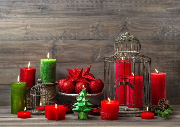 Decorazione natalizia con candele accese, palline e gabbia per uccelli. interni di casa nostalgici