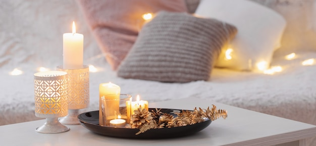 Decorazione di natale con candele accese sul tavolo bianco del divano con plaid e cuscini. casa accogliente e concetto di vacanza