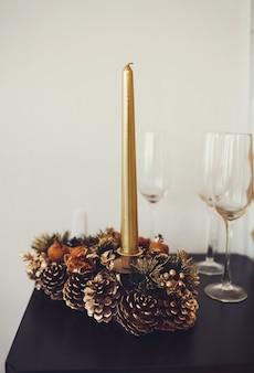 Decorazione natalizia con candela e pigne