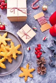 Decorazioni natalizie con coni, biscotti, scatole regalo, candele rosse, caramelle. vista dall'alto.