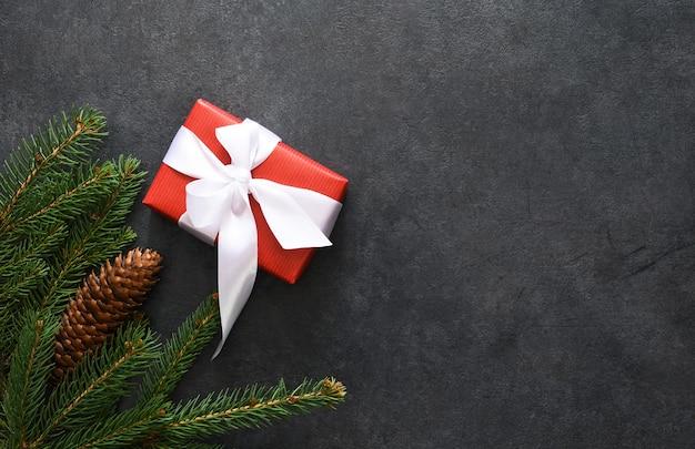 Decorazione natalizia con abete e regali su nero, piatto laici