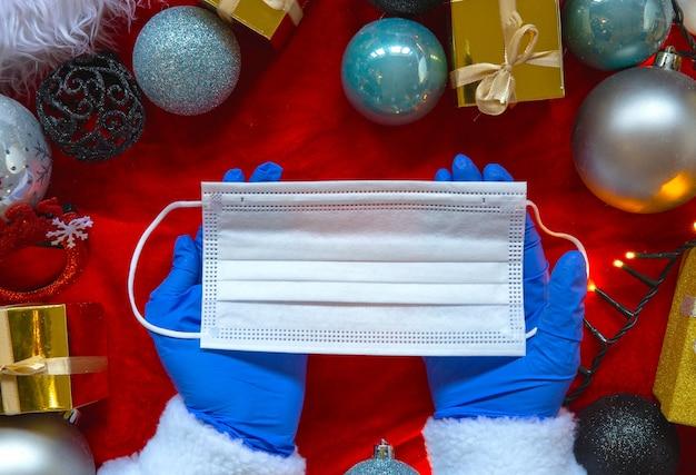 Decorazioni natalizie con guanti blu medicali e maschera protettiva per covid-19, flat lay