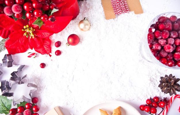 Decorazioni natalizie con fiori di poinsettia, mirtilli rossi, coni, biscotti. vista dall'alto. copia spazio.