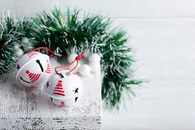 Decorazioni natalizie con campane tintinnio bianche su fondo rustico bianco. copi lo spazio per i saluti