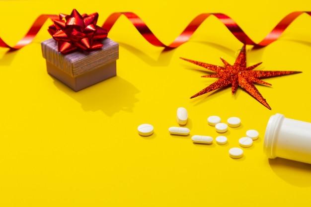 Decorazione natalizia con pillole bianche e bottiglia come simbolo di celebrazione dell'infezione da covid19