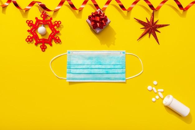 Decorazione natalizia con pillole bianche e maschera protettiva come simbolo di celebrazione con covid