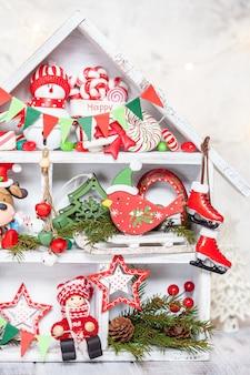 Decorazione natalizia con casetta in legno e giocattoli