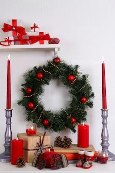 Decorazione natalizia con ghirlanda, candele e scatole regalo sullo scaffale sul muro bianco