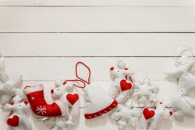 Decorazione di natale sui precedenti di legno. piatto disteso con campana fatta a mano, cari, fiocchi di neve di colore bianco