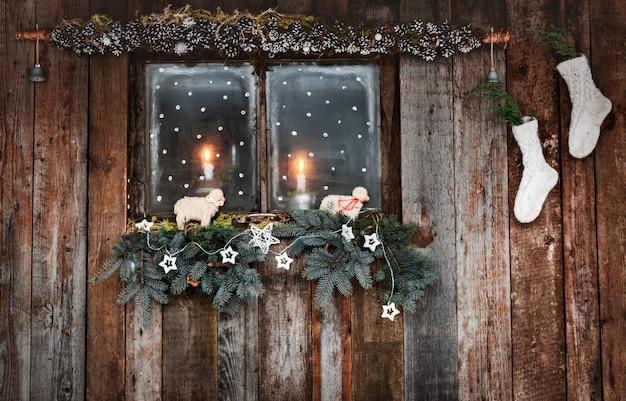 Decorazioni natalizie di pareti in legno e finestre in stile rustico. rami di conifere e calzini bianchi a lume di candela attraverso la finestra accogliente.