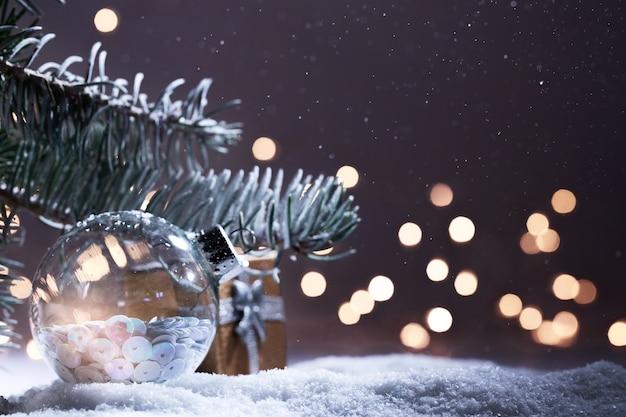 Banner di decorazioni natalizie. ramo di abete innevato con bokeh di luci di natale di notte. sfondo panoramico. composizione di natale. vacanze di capodanno 2020