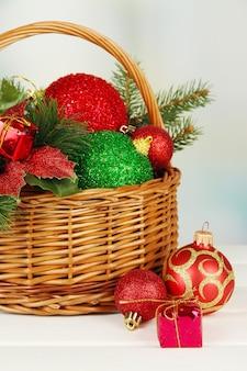 Decorazioni natalizie in cesto e rami di abete rosso sul tavolo su parete luminosa
