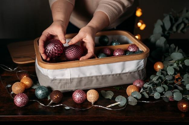 Decorazioni natalizie in scatola. le mani della donna che prendono le bagattelle di natale. sfondo scuro