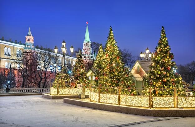 Decorazioni natalizie su alberi di natale e case in piazza manezhnaya a mosca vicino al cremlino in una notte invernale di neve