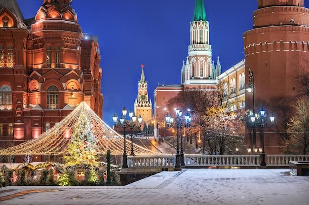 Decorazioni natalizie sugli alberi di natale in piazza manezhnaya a mosca vicino al cremlino in una notte d'inverno nevoso