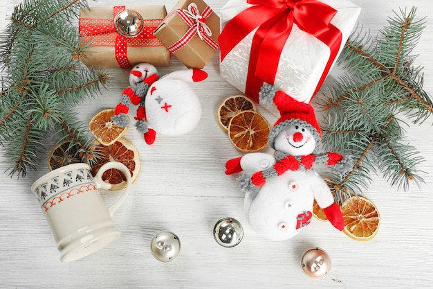 Decorazioni natalizie, coni, scatole regalo su tavolo di legno bianco
