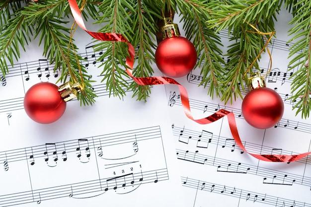 Decorazioni natalizie e ramo di abete sdraiato sul foglio di note
