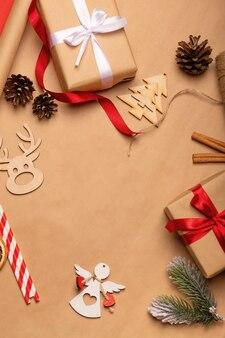 Decorazioni natalizie flatlay, regali kraft, nastro rosso, giocattoli in legno. natale concetto di sfondo