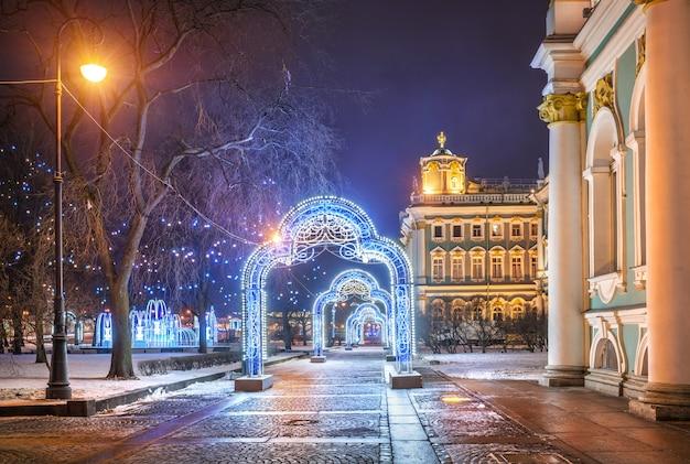 Decorazioni natalizie a forma di archi vicino all'ermitage di san pietroburgo in una notte d'inverno