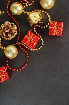 Decorazioni natalizie in oro e rosso su sfondo nero con spazio libero. vista dall'alto. atmosfera natalizia.
