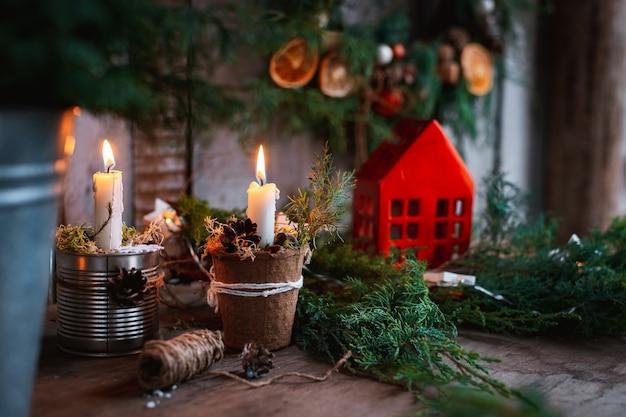 Candele fatte a mano con decorazioni natalizie. alberi di natale tessili fatti a mano per una tavola festiva con le tue mani.