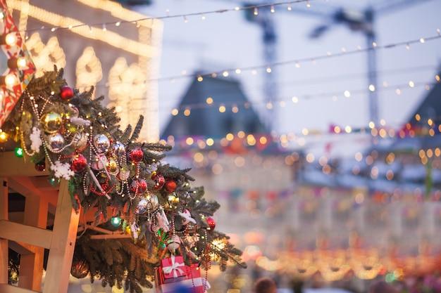 Decorazioni natalizie e albero di capodanno con luci colorate su una strada della città durante l'inverno festivo fiera. concetto di vacanze di natale