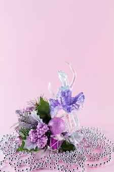 Decorazioni natalizie su sfondo rosa. figura di ballerina e perline di natale per un biglietto di auguri. anno nuovo concetto. copia spazio