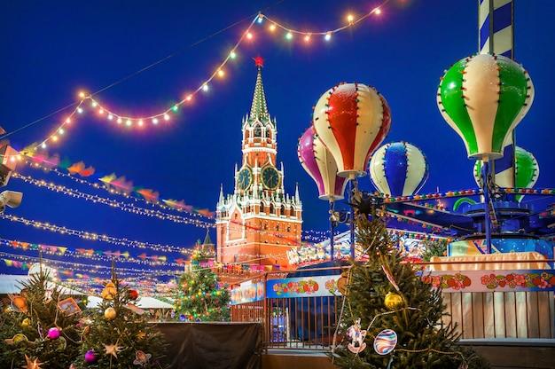 Decorazioni natalizie sulla piazza rossa di mosca e sulla torre spasskaya del cremlino alla luce dell'illuminazione notturna