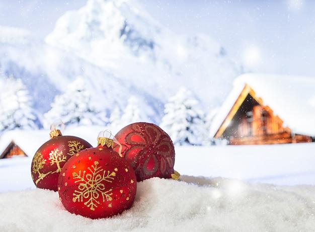 Addobbi natalizi in un cumulo di neve di fronte a montagne innevate superficie natalizia invernale